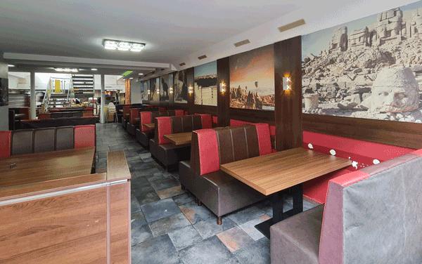 Viele Sitzplätze an mehreren Holztischen, Sitzbänke mit rot, braunem Lederbezug, in einem höhergestelltem, über eine kleine Treppe, hell beleuchtetem Sitzbereich mit Fliesenboden. An der Wand große, prachtvolle Bilder mit türkischen Monomentalmotiven.