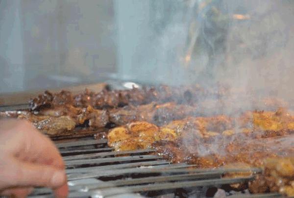 Grill mit verschieden aufgelegten Fleischspießen, es ist am qualmen.