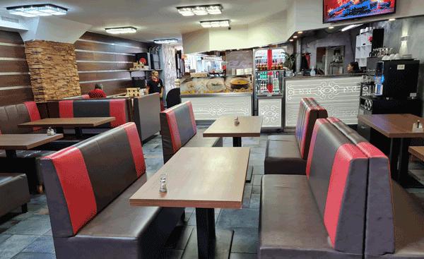 Viele Sitzplätze an mehreren Holztischen, Sitzbänke mit rot, braunem Lederbezug, in einem hell beleuchtetem Sitzbereich mit Fliesenboden