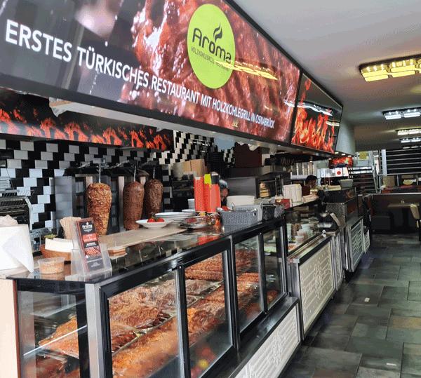 Eingangsbereich des Aroma Restaurants mit großer Theke, sowieso Kühlvitrinen mit Adanaspießen und Gemüse